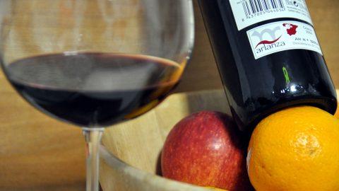 Botella de vino Arlanza, copa con vino y fruta.